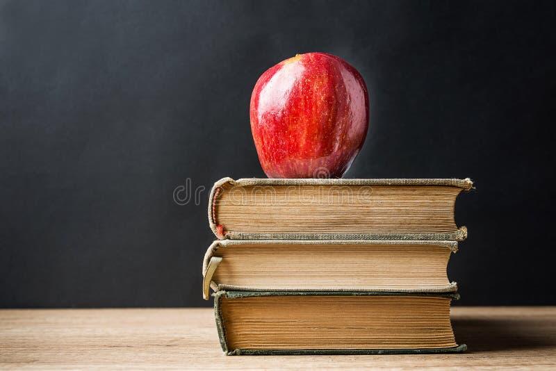 堆堆旧书在上面的红色光滑的苹果计算机 学会教育知识概念 黑板背景 Classrom 免版税库存照片