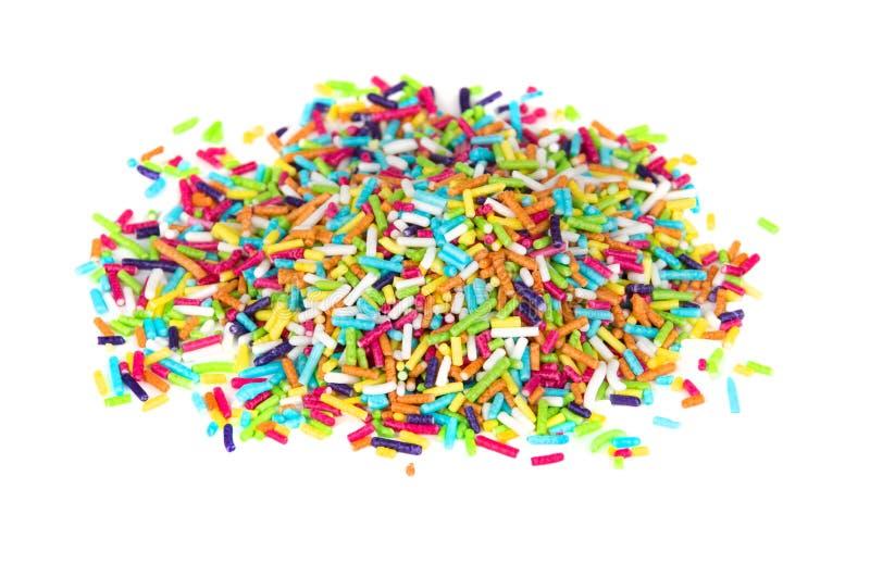 堆多色洒在白色隔绝的糖 库存照片