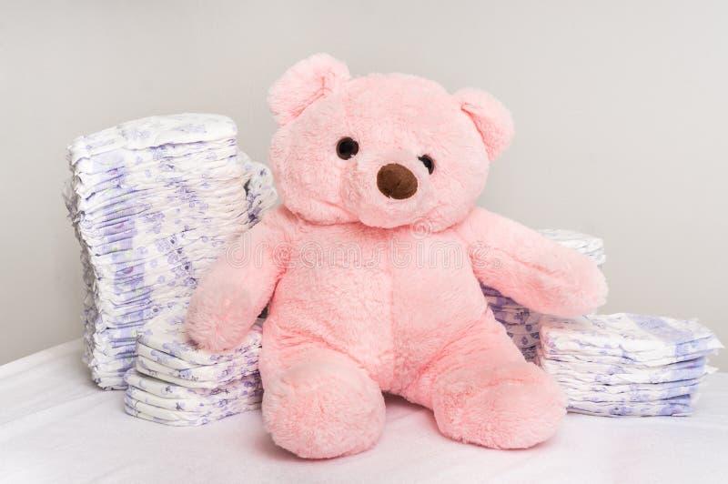 堆尿布或尿布与桃红色玩具熊 库存图片