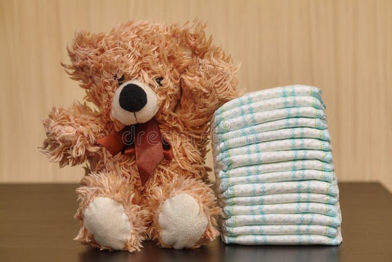 堆尿布或尿布与玩具熊 图库摄影