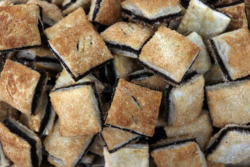 堆巧克力和糖涂上了许多饼干 免版税库存照片