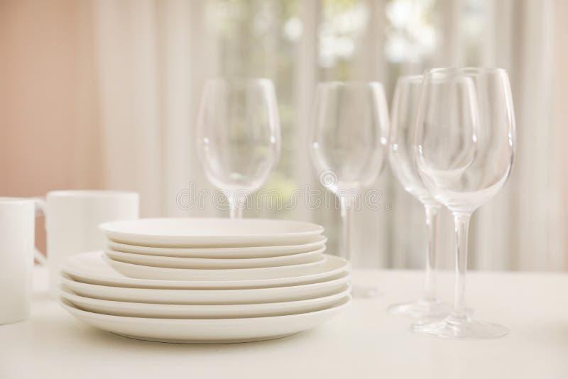 堆干净的盘、玻璃和杯子在桌上 免版税库存照片