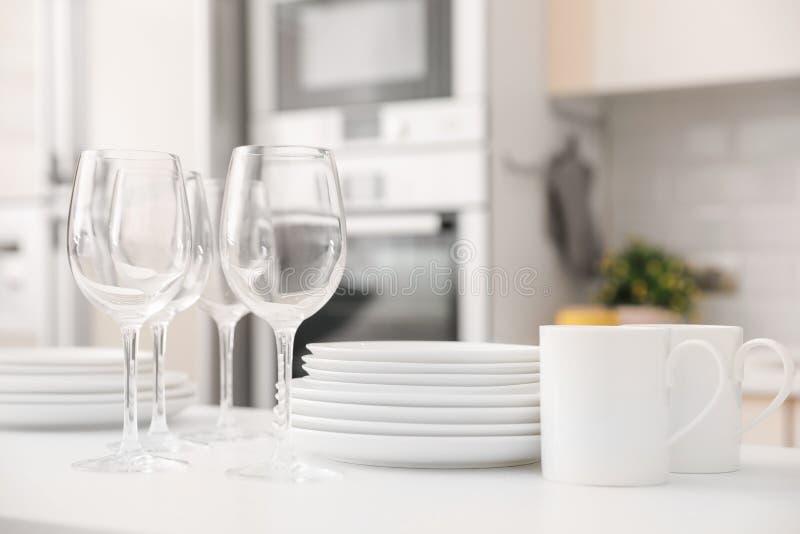 堆干净的盘、玻璃和杯子在桌上 库存图片