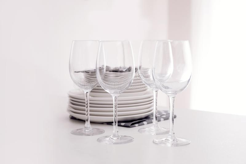 堆干净的盘和玻璃在桌上 免版税库存图片