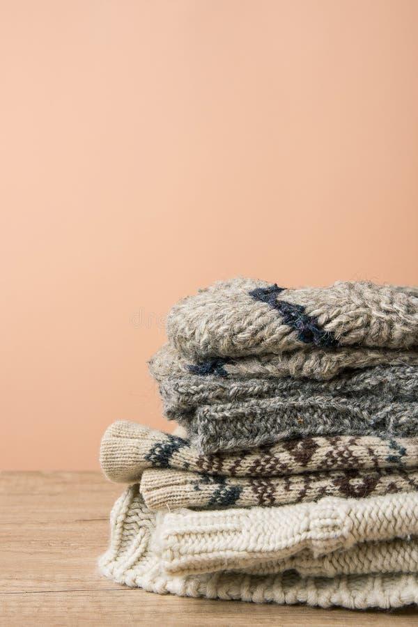 堆手工制造温暖从概略的毛纱布朗米黄灰色的被编织的袜子围巾手套毛线衣 木表桃子颜色墙壁 免版税库存照片