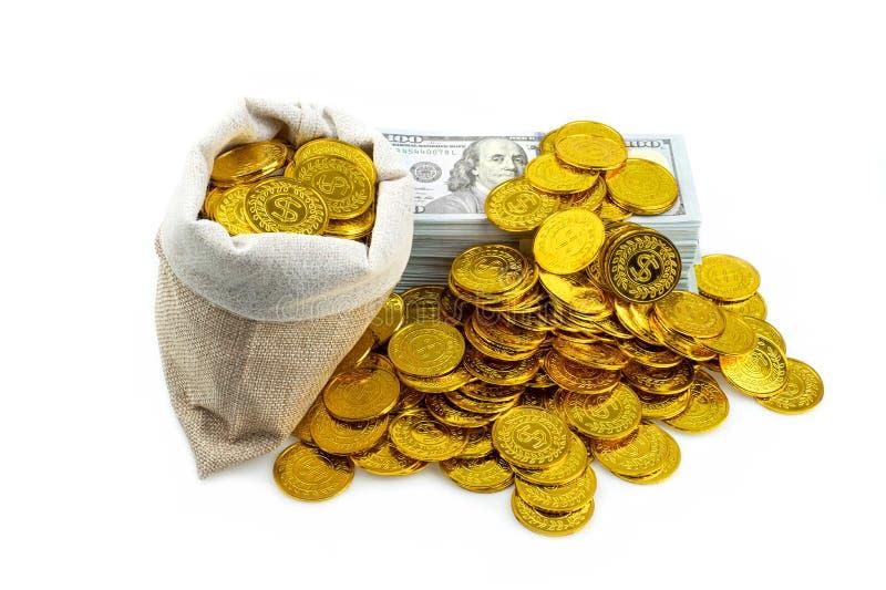 堆捆绑100枚美元钞票和金币在珍宝大袋在白色背景 库存照片