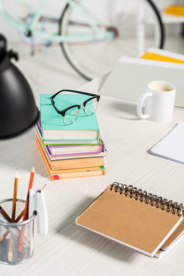 堆接近的看法书、笔记本、文件夹、在工作场所的咖啡和镜片 免版税库存照片