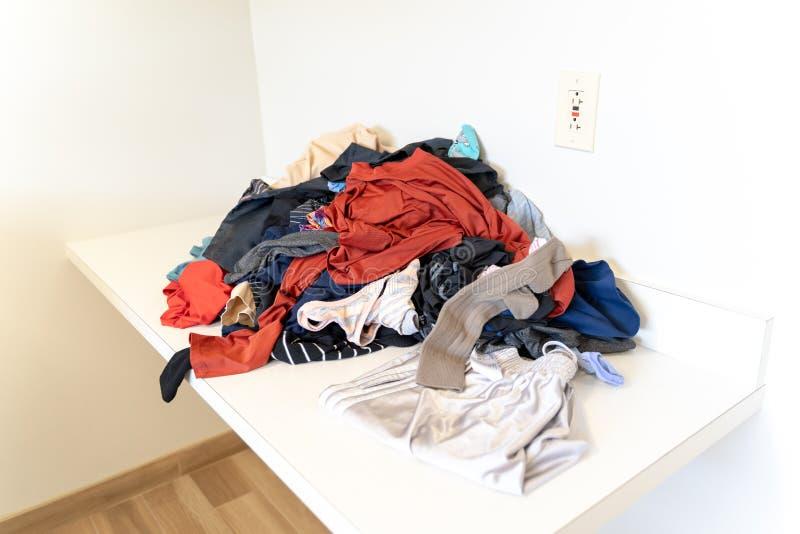 堆新近地被洗涤的衣物,准备好被折叠,在堆坐一个白色折叠式小桌在洗衣房 库存图片