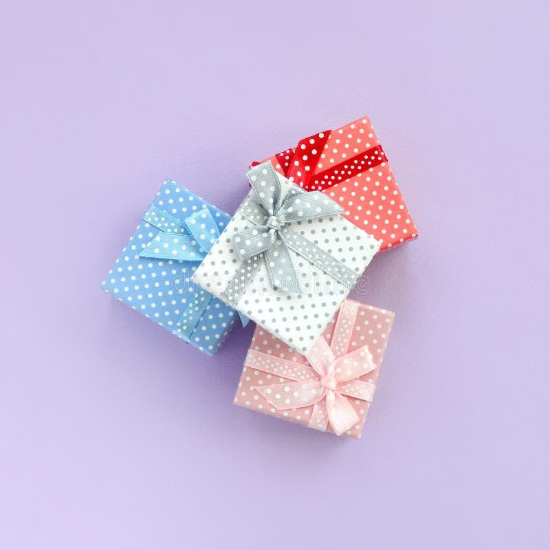 堆有丝带谎言的小色的礼物盒在紫罗兰色背景 简单派平的位置顶视图 图库摄影