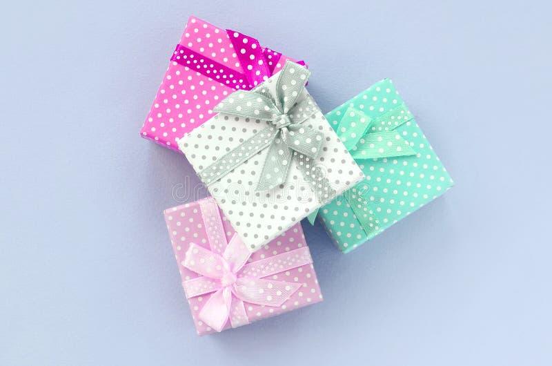 堆有丝带谎言的小色的礼物盒在紫罗兰色背景 图库摄影