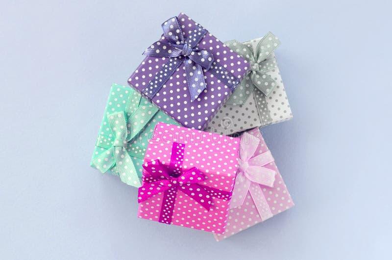 堆有丝带谎言的小色的礼物盒在紫罗兰色背景 免版税库存图片