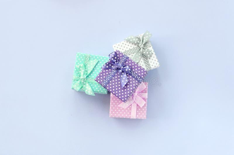 堆有丝带谎言的小色的礼物盒在紫罗兰色背景 免版税图库摄影