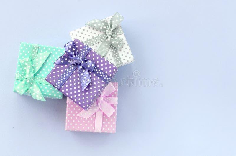 堆有丝带谎言的小色的礼物盒在紫罗兰色背景 库存图片