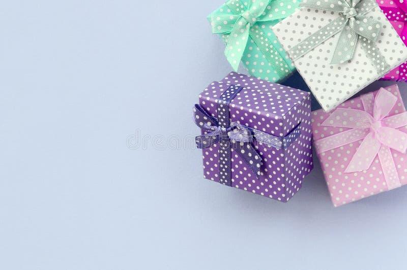 堆有丝带谎言的小色的礼物盒在紫罗兰色背景 库存照片