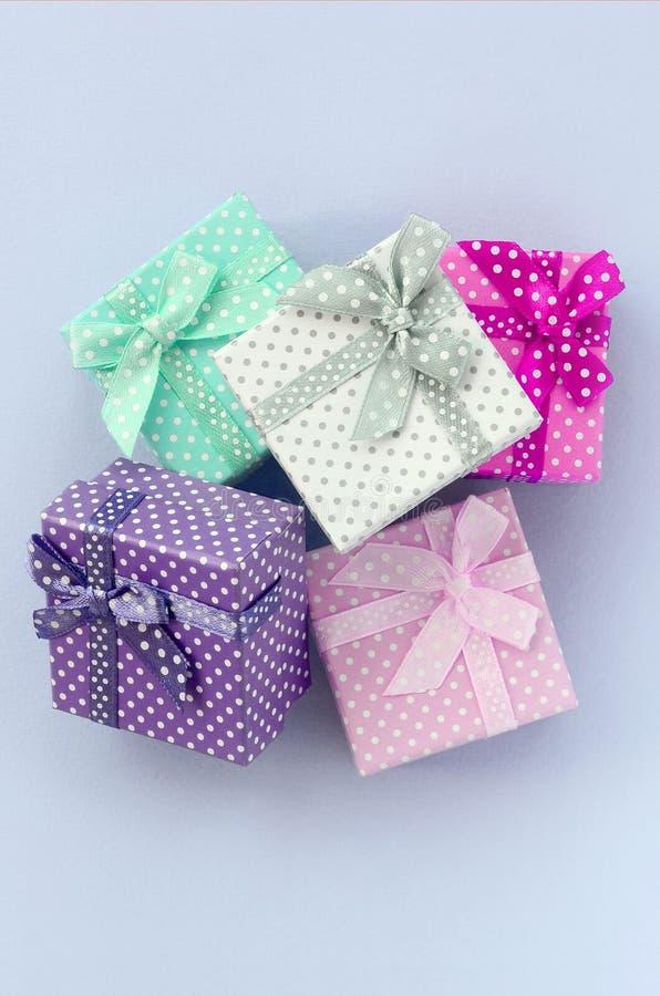 堆有丝带谎言的小色的礼物盒在紫罗兰色背景 免版税库存照片