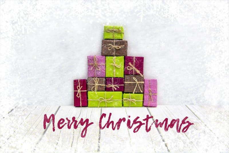 堆有礼物的五颜六色的假日箱子在与雪的白色背景和雪花、圣诞快乐和新年好概念 免版税库存照片