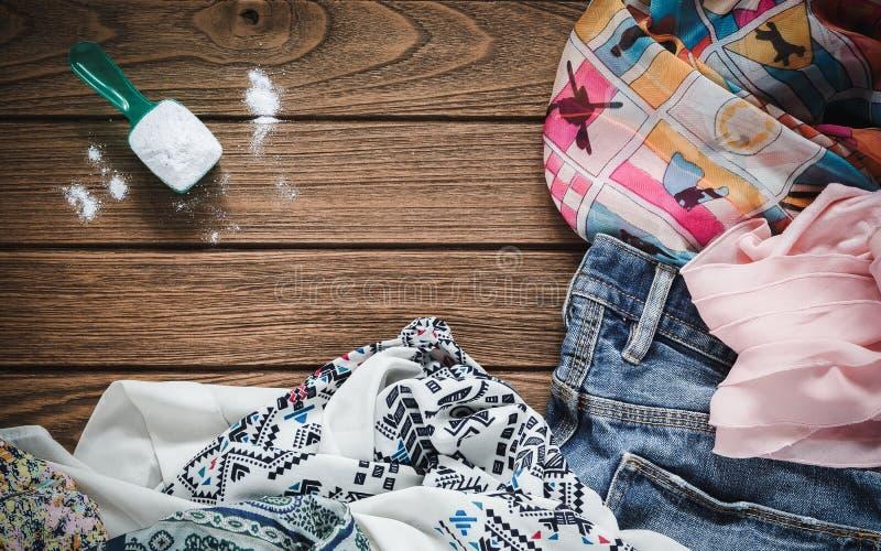 堆有洗涤剂和洗衣粉的衣裳 免版税图库摄影