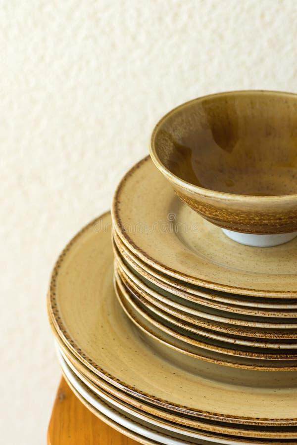 堆棕色有斑点的给上釉的陶器陶瓷板材盘和碗在木桌上 白色墙壁背景 免版税库存照片