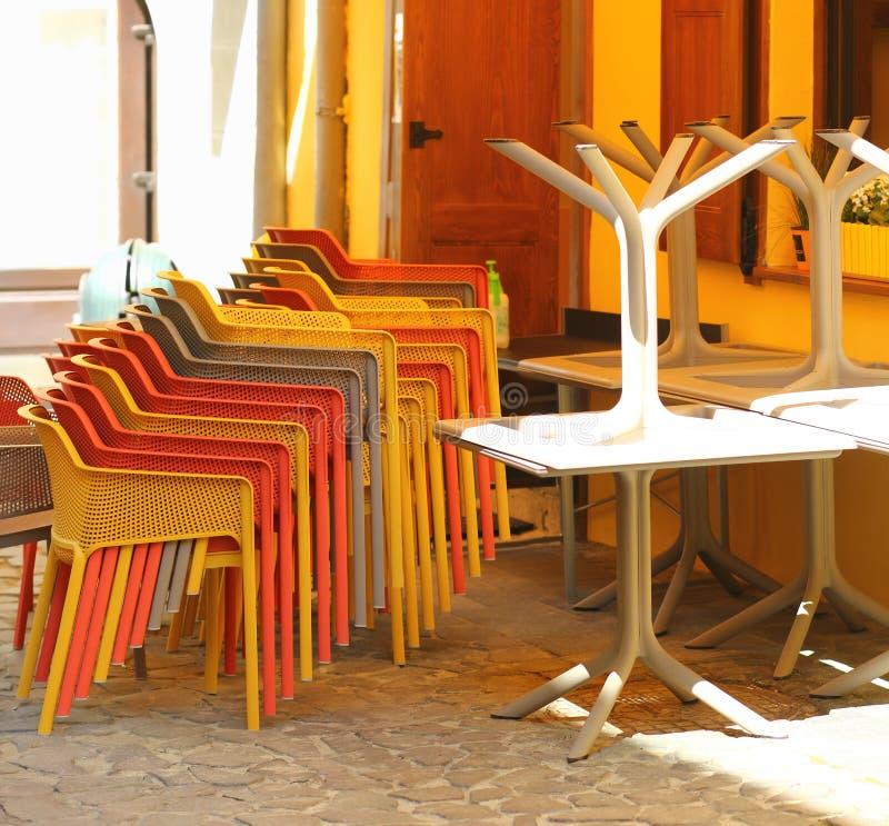 堆椅子和桌在闭合的早晨街道咖啡馆大阳台 图库摄影
