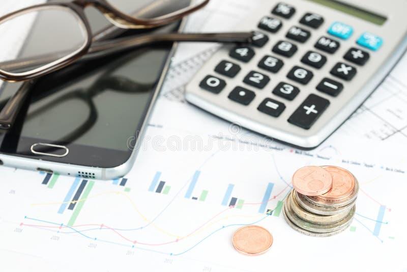堆欧洲硬币、calcualtor、电话和玻璃在financia 免版税库存照片