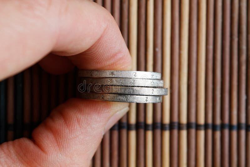 堆欧洲硬币在人` s手上在木竹桌背景 免版税库存图片