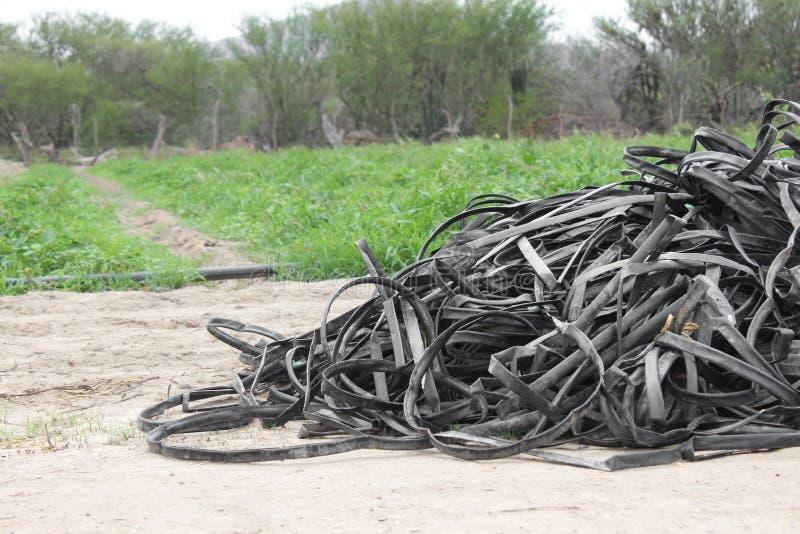 堆水滴灌溉的被放弃的磁带恶化,准备好是农业被放弃的领域 免版税库存照片
