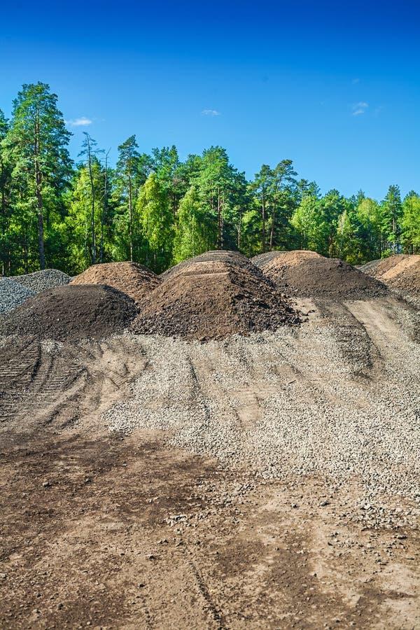堆沙子和石渣在森林里 免版税库存图片