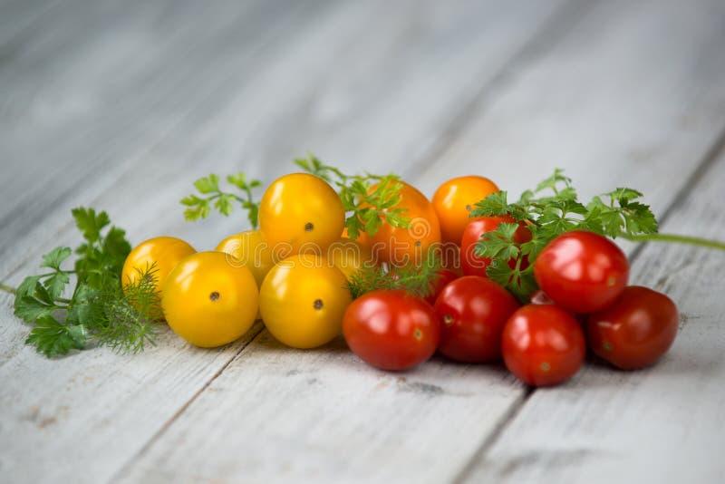堆混杂的西红柿桔子、黄色和红色用新鲜的草本在木背景 图库摄影