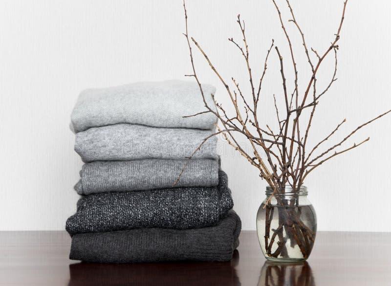 堆灰色编织了毛线衣和一个花瓶有分支的在木桌上,装饰用蜡烛 免版税库存图片