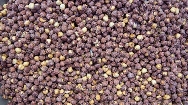 堆烤和被盐溶的,没被剥皮的榛子顶视图背景 许多棕色坚果种子、健康素食主义者和素食主义者食物 免版税库存照片