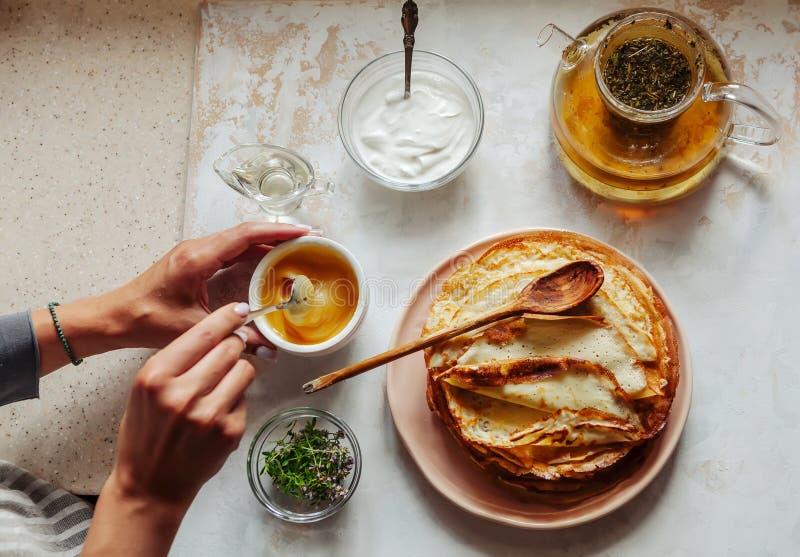堆热的经典俄国稀薄的薄煎饼 r 酸性稀奶油、黄油、绿叶、鸡蛋和茶罐在附近 库存照片