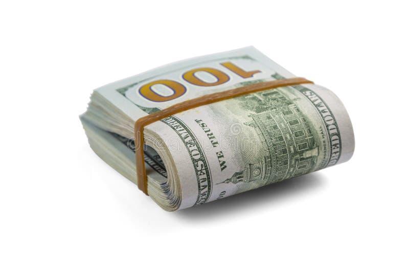 堆现金美元,在一半的倾向,在橡皮筋下在白色背景被隔绝 特写镜头 免版税库存图片