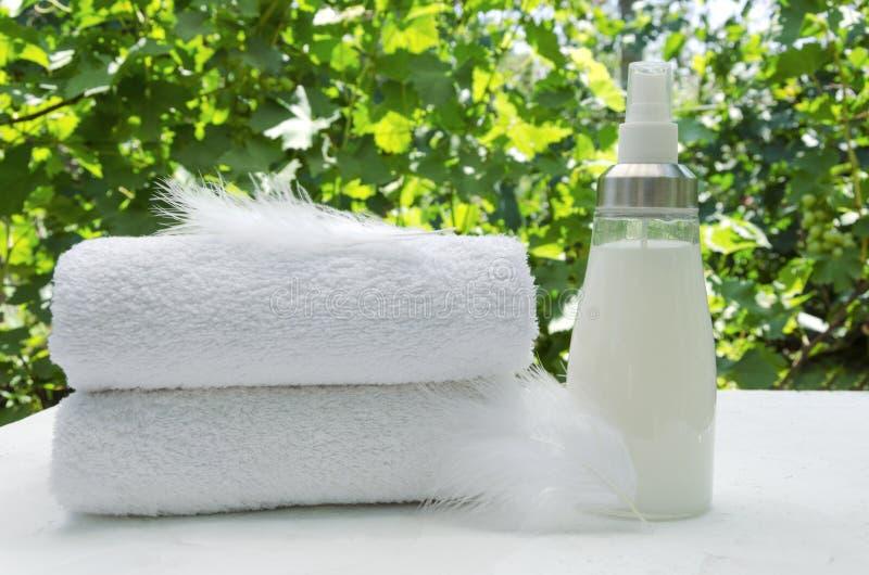 堆白色毛巾,玻璃瓶软化剂和羽毛作为精美洗涤物的标志 图库摄影