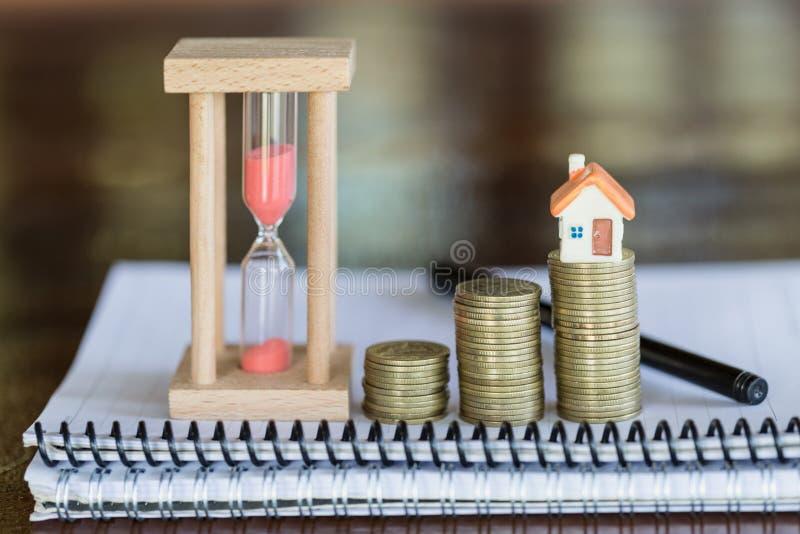 堆的微型房子硬币、金钱和房子、抵押,储款金钱购买房子的和贷款对商业投资真的 免版税库存图片