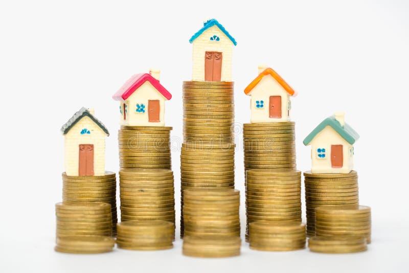 堆的微型房子硬币,隔绝在白色背景,投资物产的概念 免版税库存照片