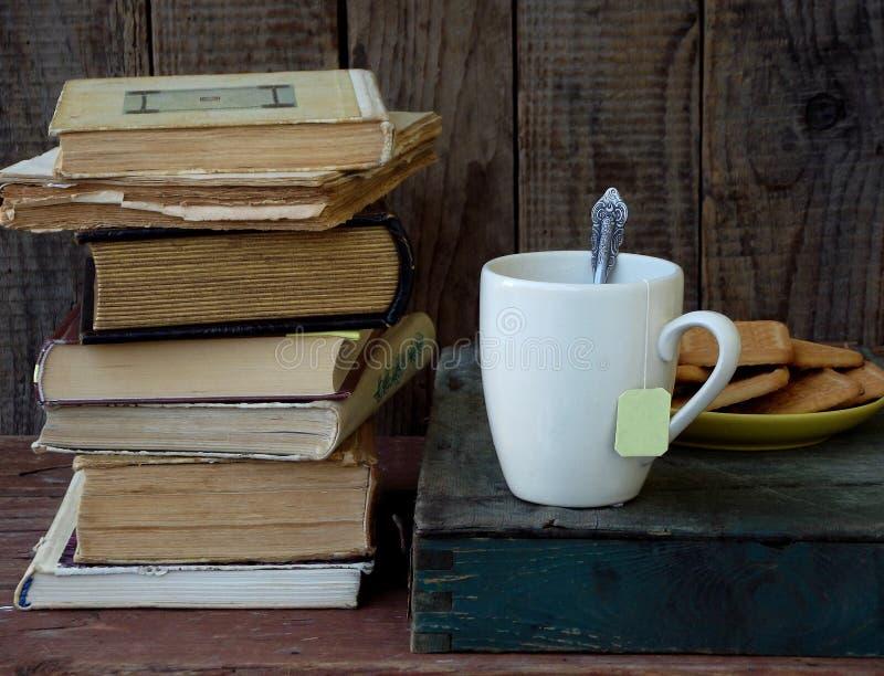 堆的构成旧书、茶杯、糖屑曲奇饼玻璃和板材在木背景的 抽象背景同类的照片结构葡萄酒 端 免版税库存图片