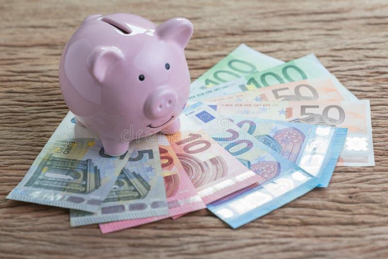 堆的桃红色存钱罐在木桌上的欧洲钞票, finan 免版税库存图片