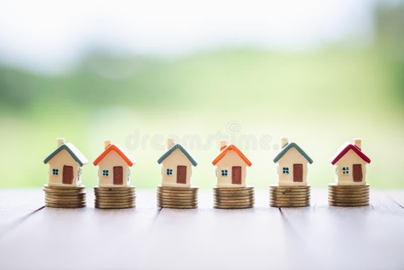 堆的硬币,投资物产、投资风险和不确定性的概念微型房子在不动产房产市场上 免版税图库摄影