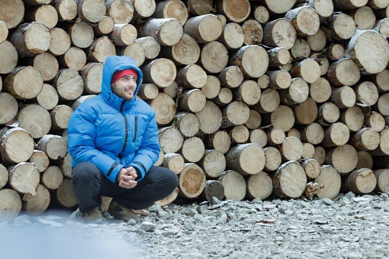 堆的蹲的伐木工人被采伐的木柴背景户外在冬天山森林里 免版税图库摄影