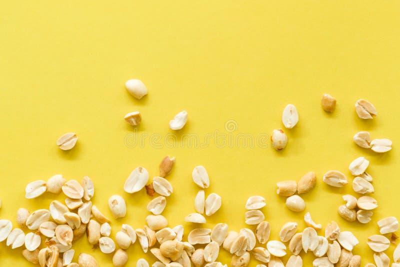 堆盐溶了并且用了卤汁泡在黄色背景隔绝的花生 免版税库存照片