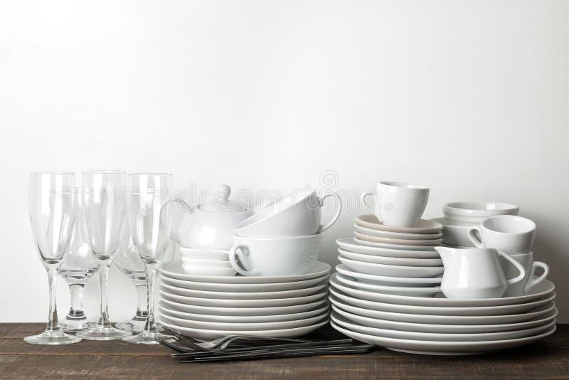 堆盘 在一张棕色木桌上的碗筷 服务的桌盘 板材和利器、杯子和茶壶,玻璃 免版税库存图片