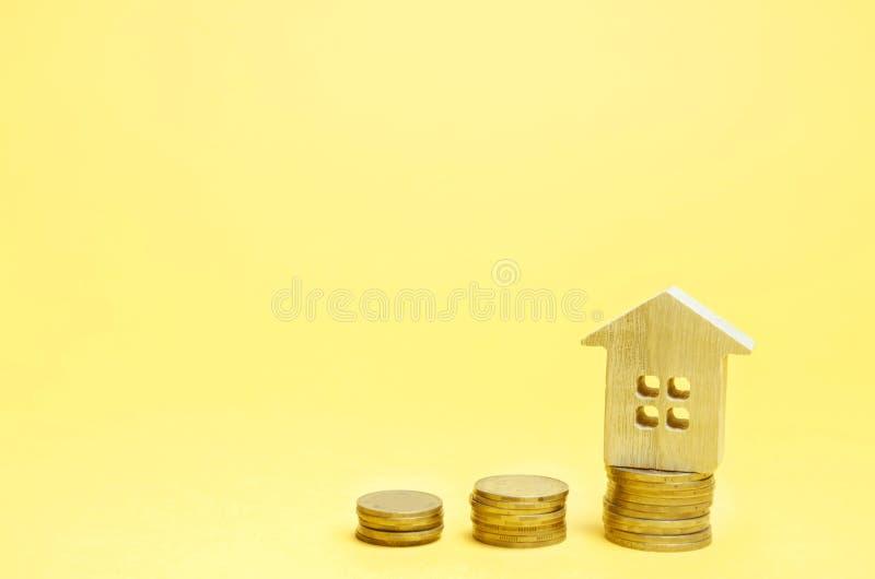 堆硬币和一个木房子 攒钱的概念买的家 买公寓,不动产 租的付款 免版税图库摄影