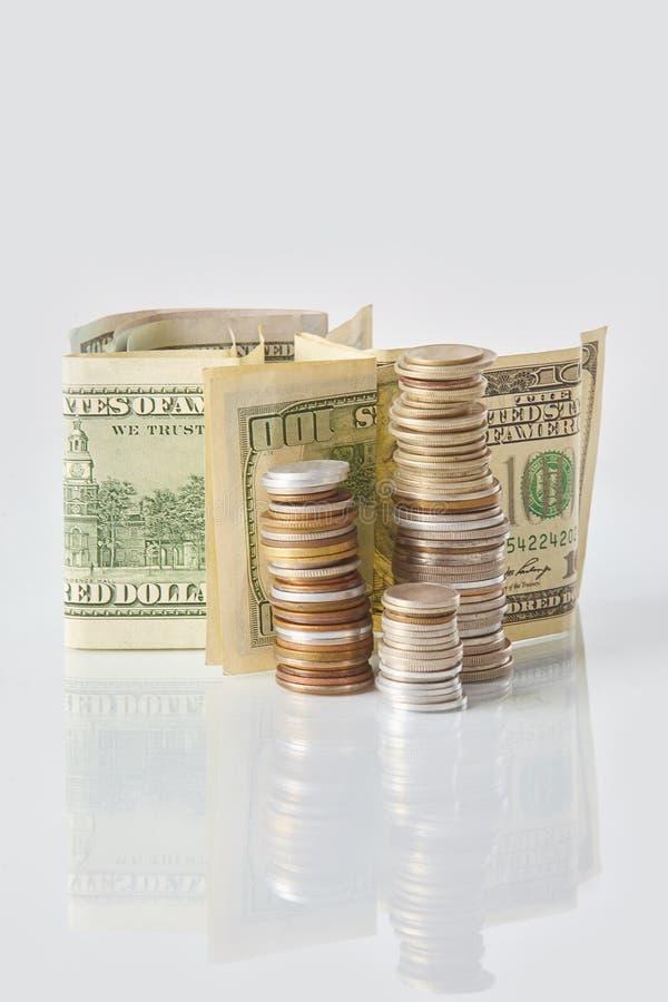 堆硬币和美金在一张白色桌上 免版税库存照片