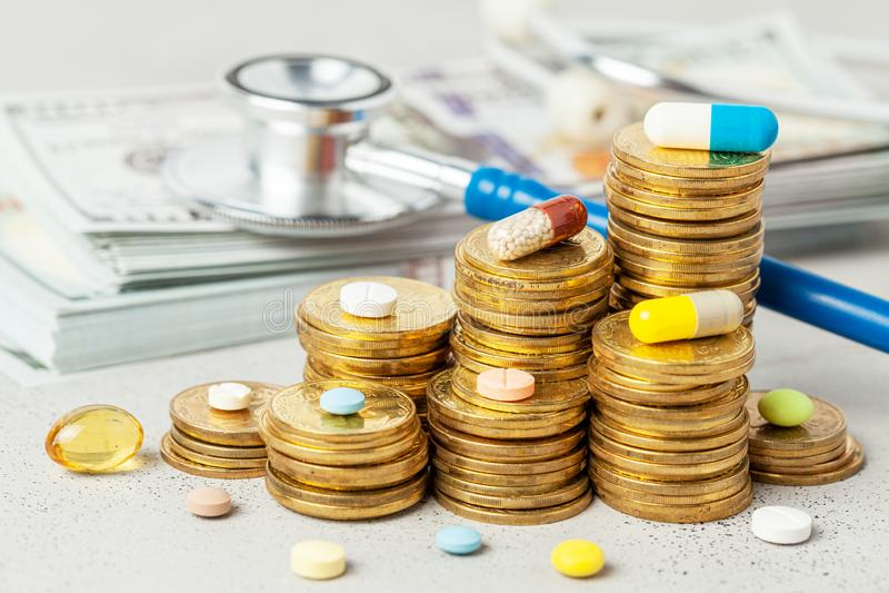 堆硬币和色的药片在灰色背景与听诊器和金钱 涨价的概念医疗的 免版税图库摄影