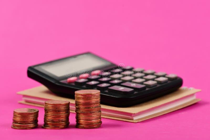 堆硬币和计算器预算计划的 在笔记本的计算器有此外金钱的在桃红色背景 库存照片