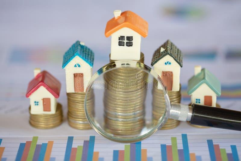 堆硬币和长条图与增长,放大镜搜寻一个新的家的,不动产的贷款或存金钱为购买房子 免版税图库摄影