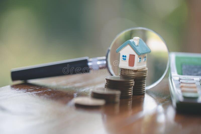 堆硬币的,放大镜搜寻一个新的家的,搜寻与放大镜的议院式样房子概念 免版税库存照片