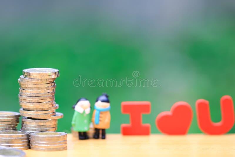堆硬币金钱和微型夫妇身分在自然绿色背景,保存为恋人或家庭和存金钱为 免版税库存图片