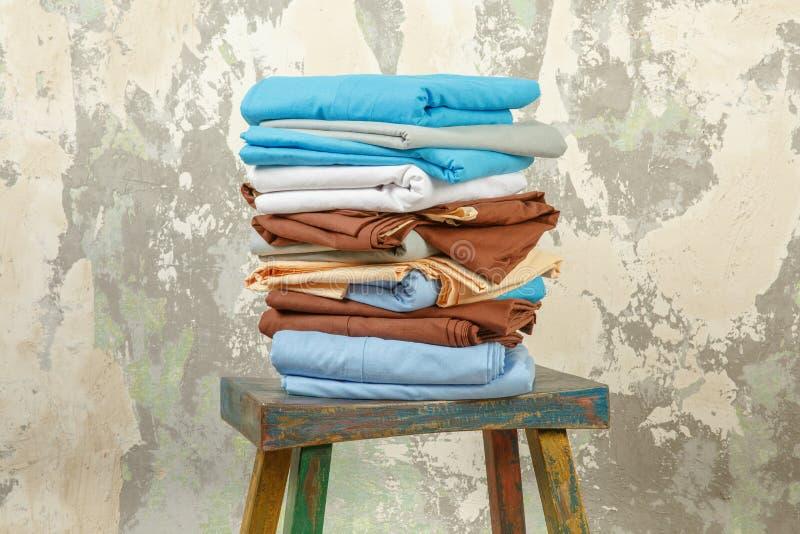 堆积五颜六色的床单纺织品衣物背景堆概念 免版税库存照片