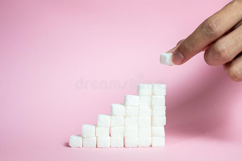 堆积从变粉红色背景的登高的糖立方体-高血糖风险的概念 免版税库存照片